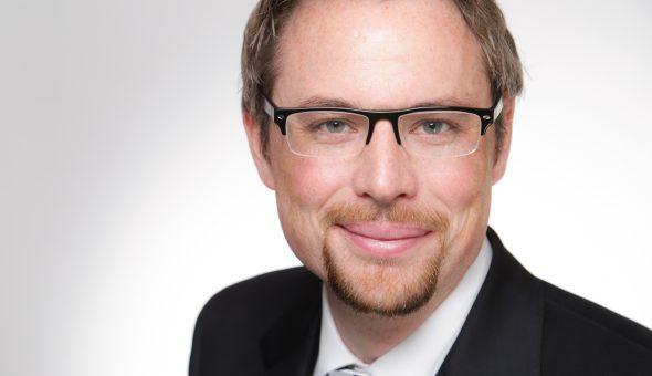 Ein Portraitbild von Tobias Dunkel im Anzug. Er trägt Brille, weißes Hemd und eine Krawatt